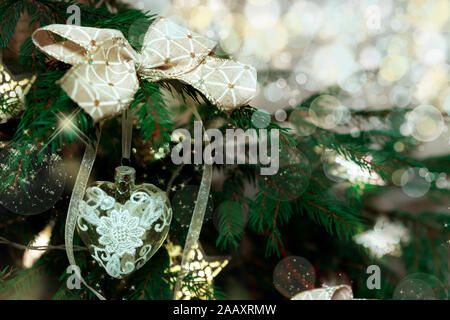 Christmas tree decorated with bows, stars, garlands on blurred, sparkling and fairy background - Stock Photo
