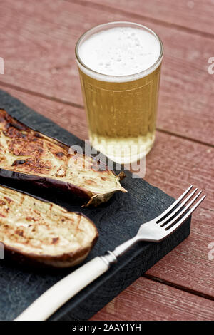 Grilled eggplant on cutting board served with beer, toned - Stock Photo