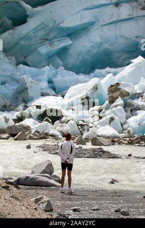 Alpine glacier in retreat - man watching - Stock Photo
