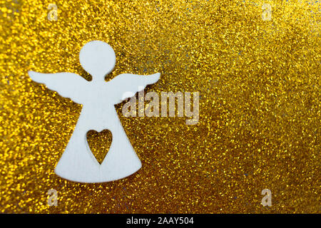 Wooden figurine of a little white angel on a shiny golden background. Copy space. Christmas holiday concept. - Stock Photo