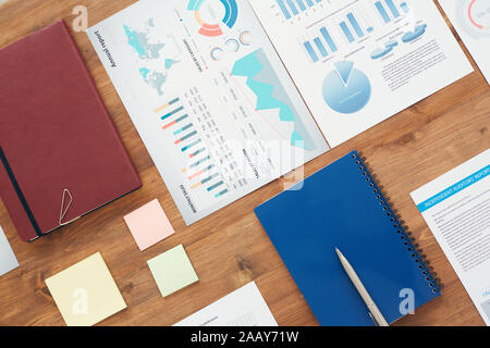 Flat lay background of office workplace with statistic graphs and documents on wooden table, copy space - Stock Photo