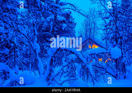 A lot of snow in the evening winter forest. Lonely wooden cottage glows in the thicket - Stock Photo