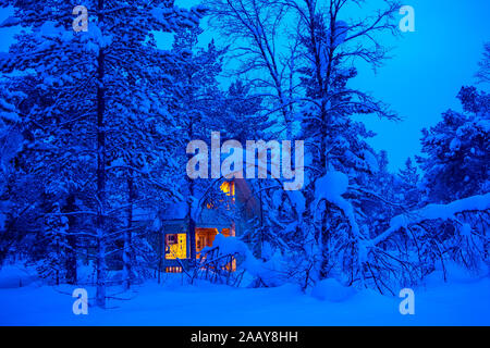 Lonely wooden cottage glows in the evening thickets of the winter forest. A lot of snow - Stock Photo