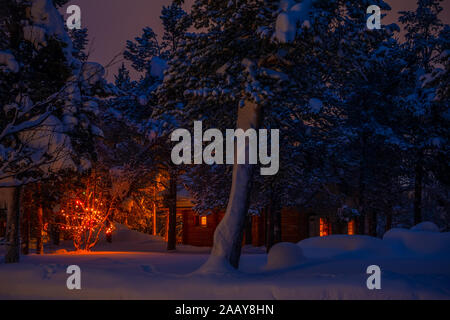 Wooden house in the night winter forest and Christmas garland. A lot of snow - Stock Photo