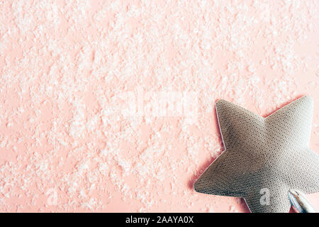 Silver christmas star for the festive tree on pastel pink snow background - Stock Photo