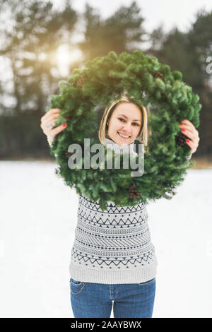 winter holidays and people concept - Happy woman holding Christmas wreath maked by herself, standing in winter forest. - Stock Photo