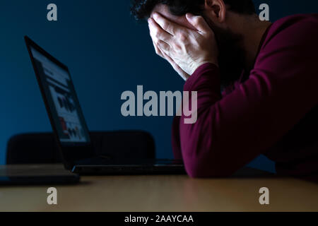Stressed young man working late on laptop, feeling frustrated and depressed covering his face with hands late in the evening