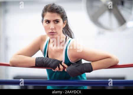 A badass female boxer is resting on ring ropes with her wraps on in a boxing gym, white walls, black and red mats, indoors. - Stock Photo