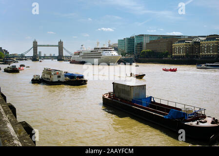 A view of Tower Bridge and the busy River Thames with barges and the ship Silver Wind moored next to the HMS Belfast. - Stock Photo