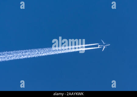 Airplanes leaving contrail trace on a clear blue sky - Stock Photo