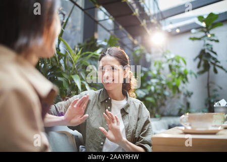 Waist up portrait of smiling young woman talking to friend on outdoor cafe terrace, copy space - Stock Photo