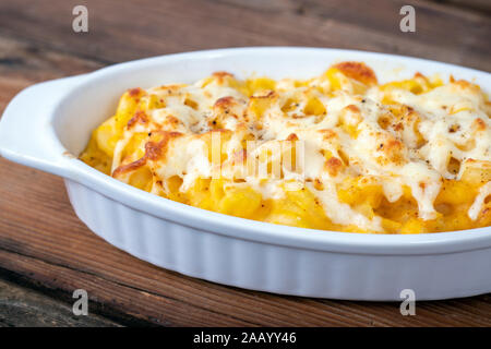 Butternut squash mac and cheese dish closeup on a rustic table and grated cheese on top - Stock Photo