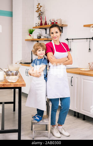 Happy adorable child and his mother in white aprons standing close to one another in the kitchen - Stock Photo