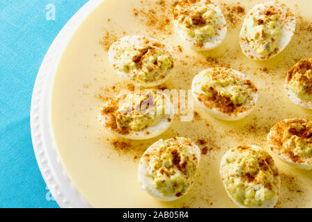 deviled egg appetizers served on double plates with a colorful tablecloth as a background. - Stock Photo