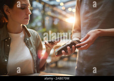 Cropped portrait of young woman paying via NFC in cafe, focus on female hands holding banking terminal, copy space - Stock Photo