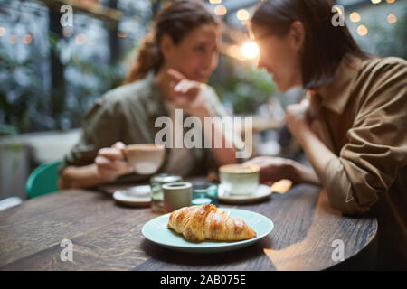 Portrait of two young women gossiping while enjoying lunch together in cafe, focus on fresh croissant in foreground, copy space - Stock Photo