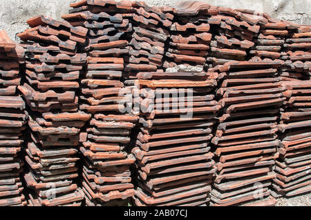 Stack of old used red terracotta Mediterranean ceramic roof tiles closeup - Stock Photo