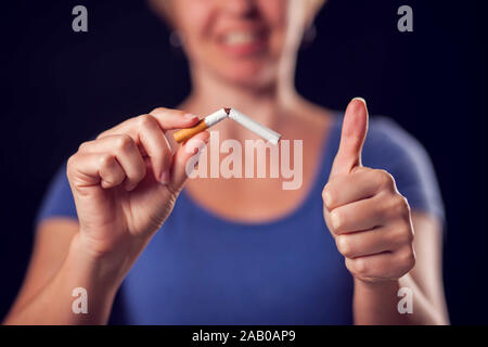 Woman in a blue t-shirt holding broken cigarette in hands. Stop smoking concept - Stock Photo