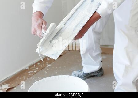 Plasterer stirring plaster in a bucket - Stock Photo