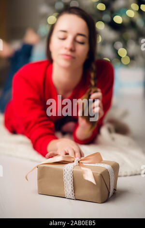 Low below angle view photo of charming cute beautiful attractive girl with a gift wearing jeans and red sweater