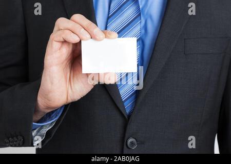 Ein Geschaeftsmann im Anzug, der eine Visitenkarte haelt - Stock Photo