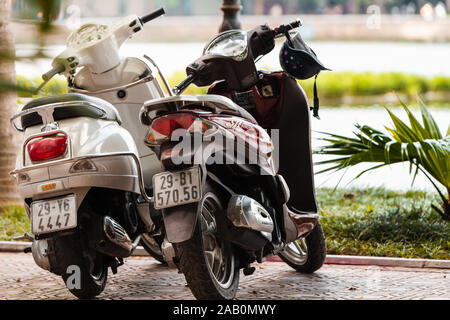 Hanoi, Vietnam - 11th October 2019: Two scooters stand in a line in Hanoi in front of a large lake on a sunny day. - Stock Photo