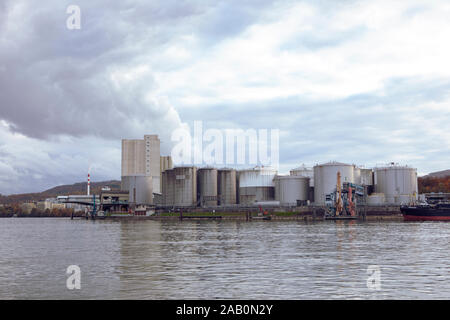 View on Rhine river with Industrial Tanks for liquid fuels storage. Industrial buildings on the bank of the river. Waterway fuel transport Switzerland - Stock Photo