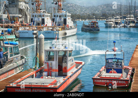 Two Harbor Patrol boats docked along with US Coast Guard ships, yachts and sailboats in the marina at the Santa Barbara Harbor,  with the Santa Barbar - Stock Photo
