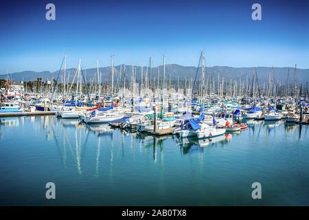A picturesque view of moored sailboats against the backdrop of the Santa Ynez Mountains at the Santa Barbara Harbor, Santa Barbara, CA, USA - Stock Photo