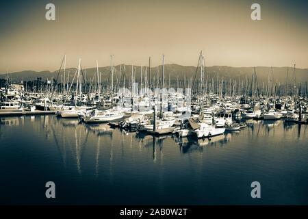 A picturesque view of moored sailboats against the backdrop of the Santa Ynez Mountains at the Santa Barbara Harbor, Santa Barbara, CA, USA, in sepia - Stock Photo