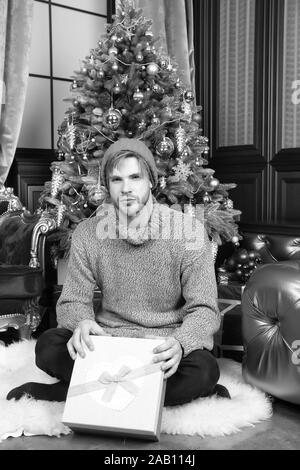 Winter holidays preparation, celebration. Man with gift box sit at Christmas tree. Macho in hat, sweater hold wrapped present. New year, xmas, eve, party. Boxing day concept. - Stock Photo