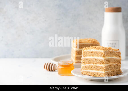 Medovik honey layer cake on white plate over grey concrete wall background. Cake slice with copy space - Stock Photo