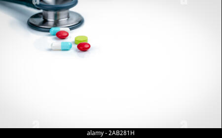 Stethoscope, capsule, and tablets pills on doctor table or nurse desk. Health checkup. Medical healthcare and medicine background. Physician tool for - Stock Photo