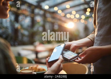 Closeup of young woman paying via NFC in cafe, focus on female hands holding smartphone with blank screen to banking terminal, copy space - Stock Photo