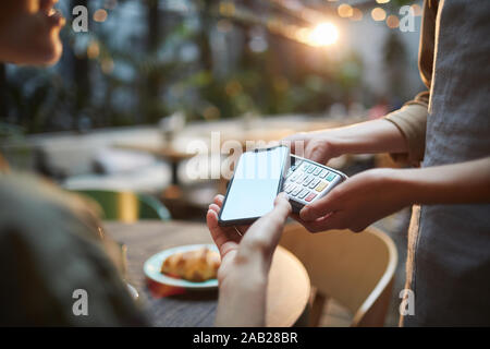 Close up of young woman paying via NFC in cafe, focus on female hands holding smartphone with blank screen to banking terminal, copy space - Stock Photo
