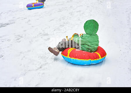 little boy sledding in winter. child slides down the mountain on a tubing - Stock Photo