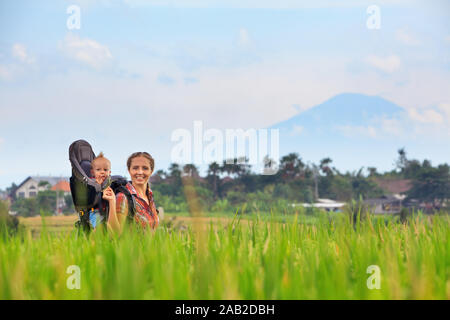 Nature walk in green rice terrace field. Happy mother hold little traveller in carrying backpack. Baby ride on woman back. Travel adventure, hiking - Stock Photo