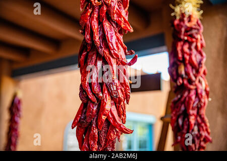 Red hot chili peppers ristras dried bunch hanging on a traditional building entrance, Santa Fe New Mexico - Stock Photo