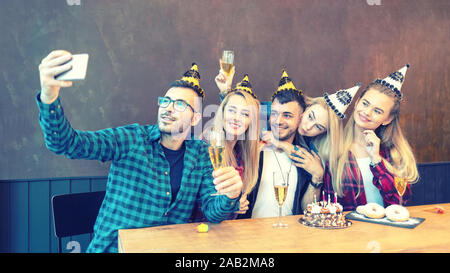 Group of best friends with festive cap taking selfie at birthday party celebrating on social media - Stock Photo
