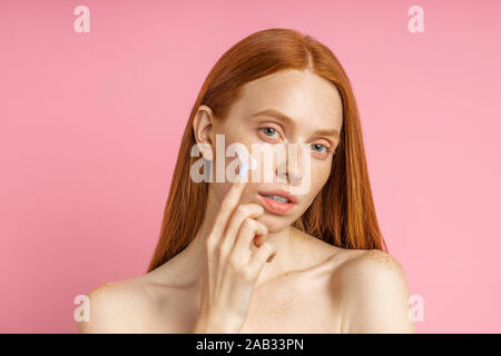 Closeup beauty portrait of redhead caucasian beautiful female applying moisturizing cream or face primer and looking at camera over pink background. Y - Stock Photo