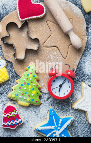 Flat lay of time for Christmas cookies preparation concept made of cutters, dough, rolling pin, biscuits with colorful icing and alarm clock on table.