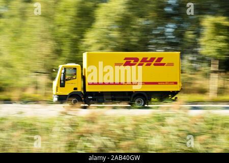 Lastkraftwagen von DHL auf dem Weg ins Logistikzentrum |DHL lorry on the way to the logistics center| - Stock Photo