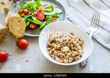 hot Buckwheat porridge with melting butter in plate andHealthy vegetarian salad of fresh vegetables for lanch on table, top view, copy space Healthy f - Stock Photo