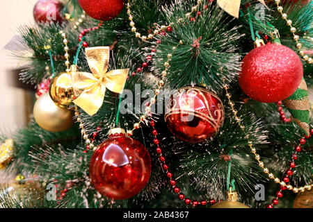 New Year colorful decoration ornaments on Christmas tree. Room decorated to christmas celebration, holiday scene with various shapes, balls on tree.