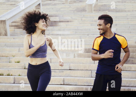 smiling woman and happy man running downstairs on city stairs, fitness, urban sports workout and healthy lifestyle concept - Stock Photo