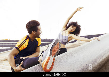 happy young man and woman stretching on city stairs before running, fitness, urban sports workout and healthy lifestyle concept, copy space for text