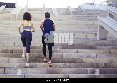 young woman and man running upstairs on city stairs, fitness, urban sports workout and healthy lifestyle concept, copy space for text - Stock Photo