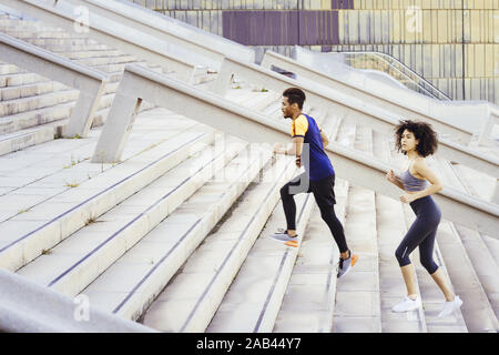 interracial couple training running up stairs in the city. fitness, urban sports workout and healthy lifestyle concept, copy space for text - Stock Photo
