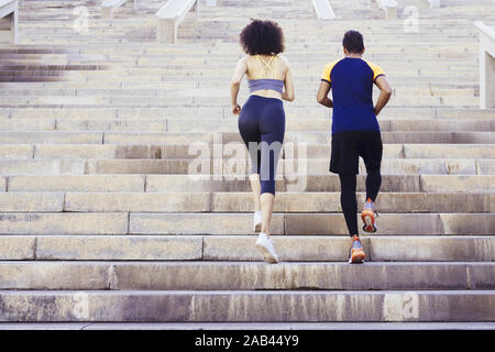 young runners couple running upstairs on city stairs, fitness, urban sports workout and healthy lifestyle concept, copy space for text - Stock Photo