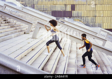 young latin sports woman and afro american man running up stairs in the city. fitness, urban sports workout and healthy lifestyle concept, copy space - Stock Photo